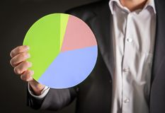 Business man holding a pie chart made from cardboard paper. Visual demonstration of finance statistics and market and sales situation Royalty Free Stock Photography