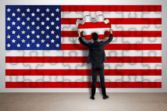 Business man holding piece of puzzle, making USA flag Royalty Free Stock Photos