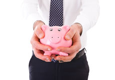 Businessman holding a piggy bank. Stock Photography