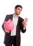 Business man holding piggy bank with Australian dollars. Vertical portrait of a business man wearing a suit holding a piggy bank and AUD Australian Dollars Royalty Free Stock Photos