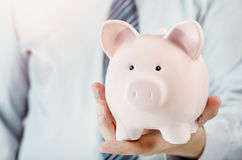 Business man holding piggy bank in hand Royalty Free Stock Photo