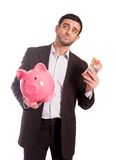 Business man holding piggy bank with money. Vertical portrait of a business man wearing a suit holding a piggy bank and AUD Australian Dollars, thinking about Royalty Free Stock Images