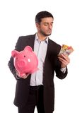 Business man holding piggy bank with money. Vertical portrait of a business man wearing a suit holding a piggy bank and AUD Australian Dollars, thinking about Royalty Free Stock Photo