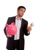 Business man holding piggy bank with money. Vertical portrait of a business man wearing a suit holding a piggy bank and money thinking about saving and his Royalty Free Stock Image