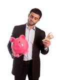 Business man holding piggy bank with money. Vertical portrait of a business man wearing a suit holding a piggy bank and money thinking about saving and his Royalty Free Stock Photography