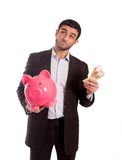 Business man holding pink piggy bank with money in hand. Vertical portrait of a business man wearing a suit holding a piggy bank and money thinking about saving Royalty Free Stock Image