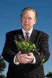 Business man holding plant. Royalty Free Stock Photography