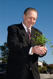 Business man holding plant. Stock Photo