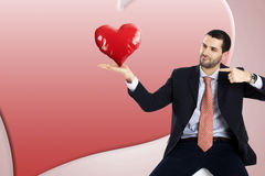 Business man is holding and pointing his heart. Business man is holding and pointing his red heart Stock Images