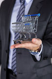 Business man holding shopping cart Royalty Free Stock Photo