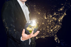 Business man holding the small world in his hands against americ Stock Image