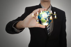 Business man holding the small world in his hands against Royalty Free Stock Photos