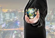 Business man holding the small world in his hands with cityscape Stock Images
