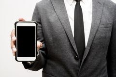 Business man holding smart phone. Business man holding a smart phone Stock Photography