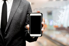 Business man holding smart phone with blur image of hall way. Business man holding a smart phone with blur image of hall way Stock Images