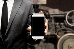 Business man holding smart phone with blur image of machine. Business man holding a smart phone with blur image of machine Royalty Free Stock Photos