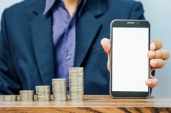 Business man holding smart phone and growing money coins. Business man holding smart phone with white screen for mock up and  growing money coins on wooden table Royalty Free Stock Photos