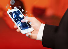 Business man holding smart phone with media icons Royalty Free Stock Images