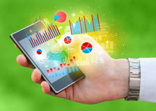 Business man holding smartphone with chart symbols Stock Images