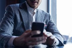 Business man holding smartphone, using application to booking suite in hotel for business trip, using wireless royalty free stock photos