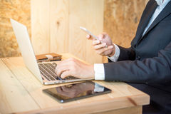 Business man holding smartphone and using laptop Stock Image