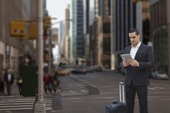Business man holding a tablet against city background Royalty Free Stock Photos