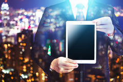 Business man holding tablet on blurry background. Stock Photo