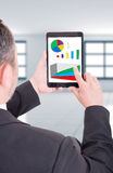 Business man holding tablet with financial charts Stock Photography