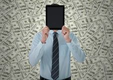 Business man holding tablet over face against money backdrop stock photo