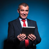 Business man holding a tablet pad and smiles Stock Photography