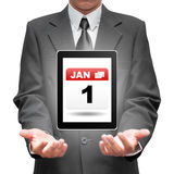 Business man holding a tablet showing 1 Jan of New Year's Day ic Stock Photography