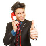 Business man holding thumbs up during phone call Stock Photo