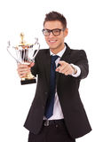 Business man holding a trophy and pointing. Happy business man holding a trophy and pointing to you over white background stock images