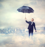 Business man holding an umbrella. On the clouds Royalty Free Stock Photo