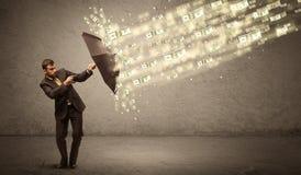Business man holding umbrella against dollar rain concept Stock Photos