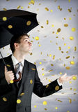 Business man holding an umbrella, money falling. From the overcast sky Royalty Free Stock Images