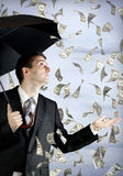 Business man holding an umbrella, money falling Stock Photography