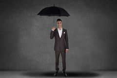 Business man holding an umbrella Stock Photos