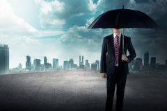 Business man holding umbrella standing on the rooftop Stock Images