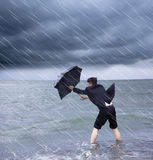 Business man holding a umbrella to resist rainstorm Stock Photo