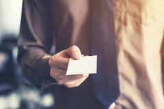 Business man holding white business card in the office. Vintage Stock Photos