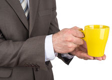 Business man holding yellow cup of black coffee Royalty Free Stock Photography