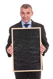Business man holds a blank blackboard Royalty Free Stock Images
