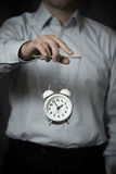 Business man holds a clock, hanging on cords, and manages it Stock Photos