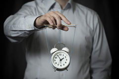 Business man holds a clock, hanging on cords, and manages it Stock Images