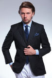 Business man holds hand on suit button royalty free stock photography