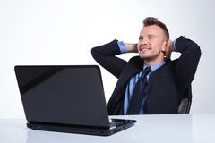 Business man holds hands behind head. Young business man relaxing at the laptop with his hands behind his head and looking away with a smile on his face. on a Stock Image