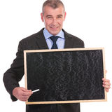 Business man holds a small blackboard and points with chalk Stock Images