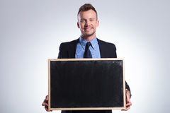Business man holds a small chalkboard Royalty Free Stock Image