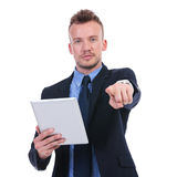Business man holds tablet and points at you Royalty Free Stock Images